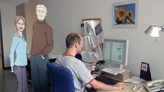 A man working next to two cardboard cutouts of personas.
